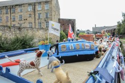 PIC BY BEN FURST/MERCURY PRESS (PICTURED: A CANAL BOAT IS DECORATED WITH FLAGS,DOGS AND VARIOUS OBJECTS These beautiful pictures show families flooding the banks of Burnley canal to mark the 200th birthday of the Leeds-Liverpool waterway this Bank Holiday weekend. Artists joined dancers, bands, boaters and residents to stage a 'creative revolution' with an explosion of colour, art and family fun for this year's Burnley Canal Festival. To celebrate the bicentenary of the 127-mile canal, festival participants donned traditional Victorian dress while venues along the water were adorned with new artworks and performances. And while a myriad of colourful boats and barges filled the waterway, kids had the chance to decorate their own less water-resistant vessel made of cardboard. Drawing on the heritage of Burnley as a vital cog in the wheel on industrialisation, revellers were also treated to maypole dancing, Punch and Judy shows and folk dancing. SEE MERCURY COPY